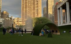 The GREEN's arches covered in synthetic grass stand in front of the city skyline.