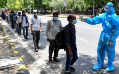 People in India line up to get their temperatures checked, wearing masks and standing 2 m apart