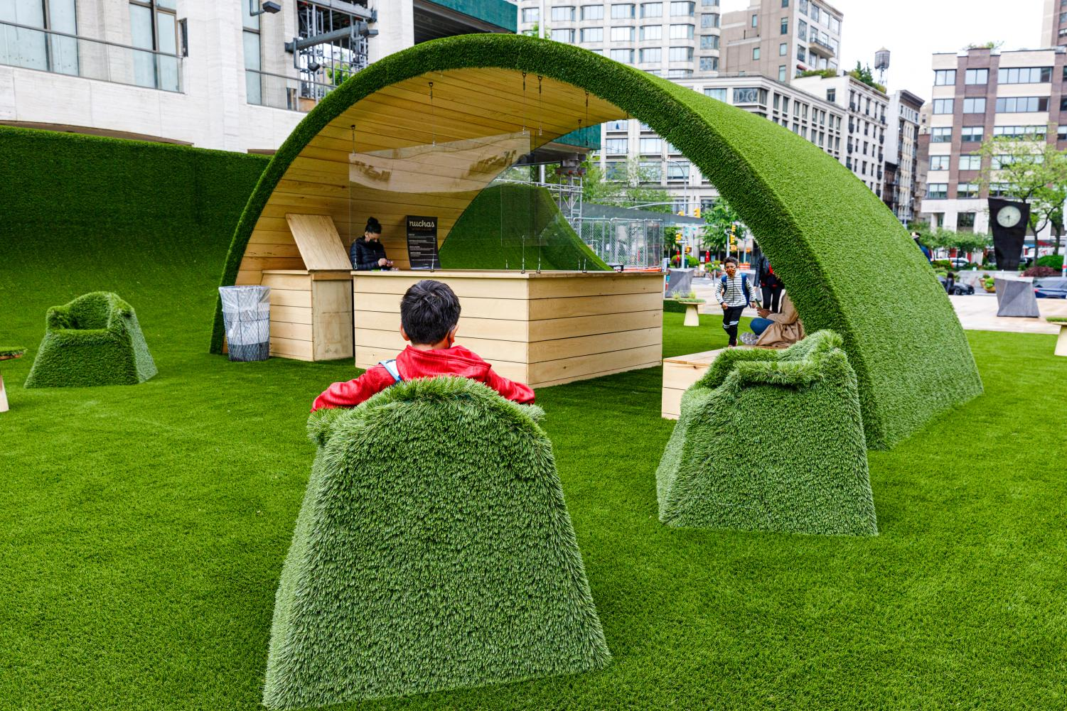 A child sits in a green grass chair in front of one of the grassy arches at The GREEN.