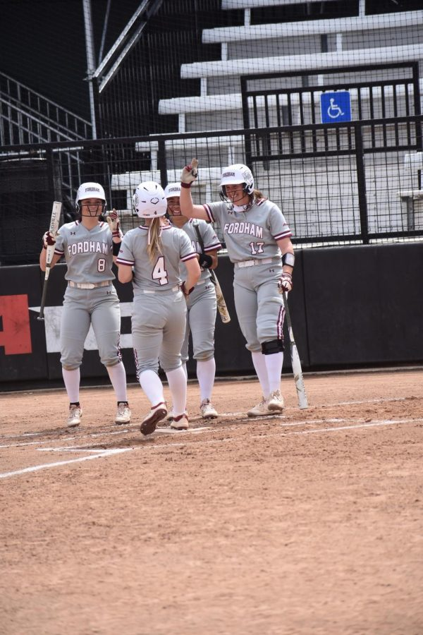 Fordham softball players celebrating on a field.