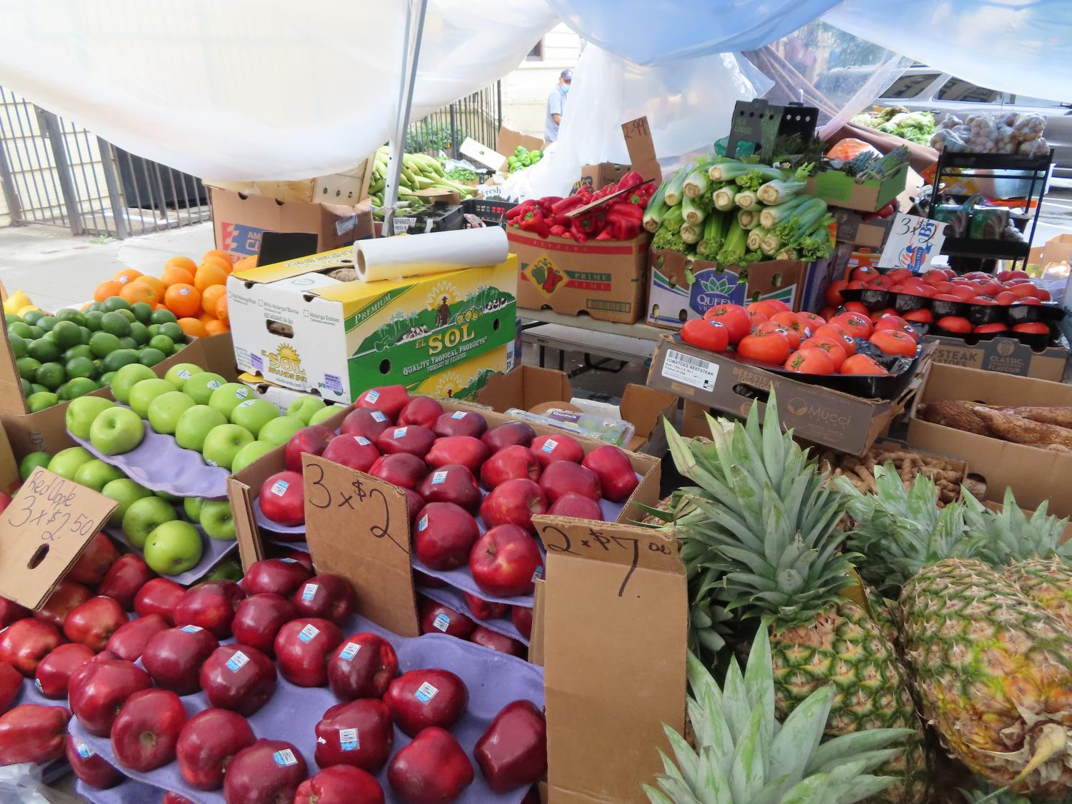 fresh fruit, including apples and pineapples, on display in a market