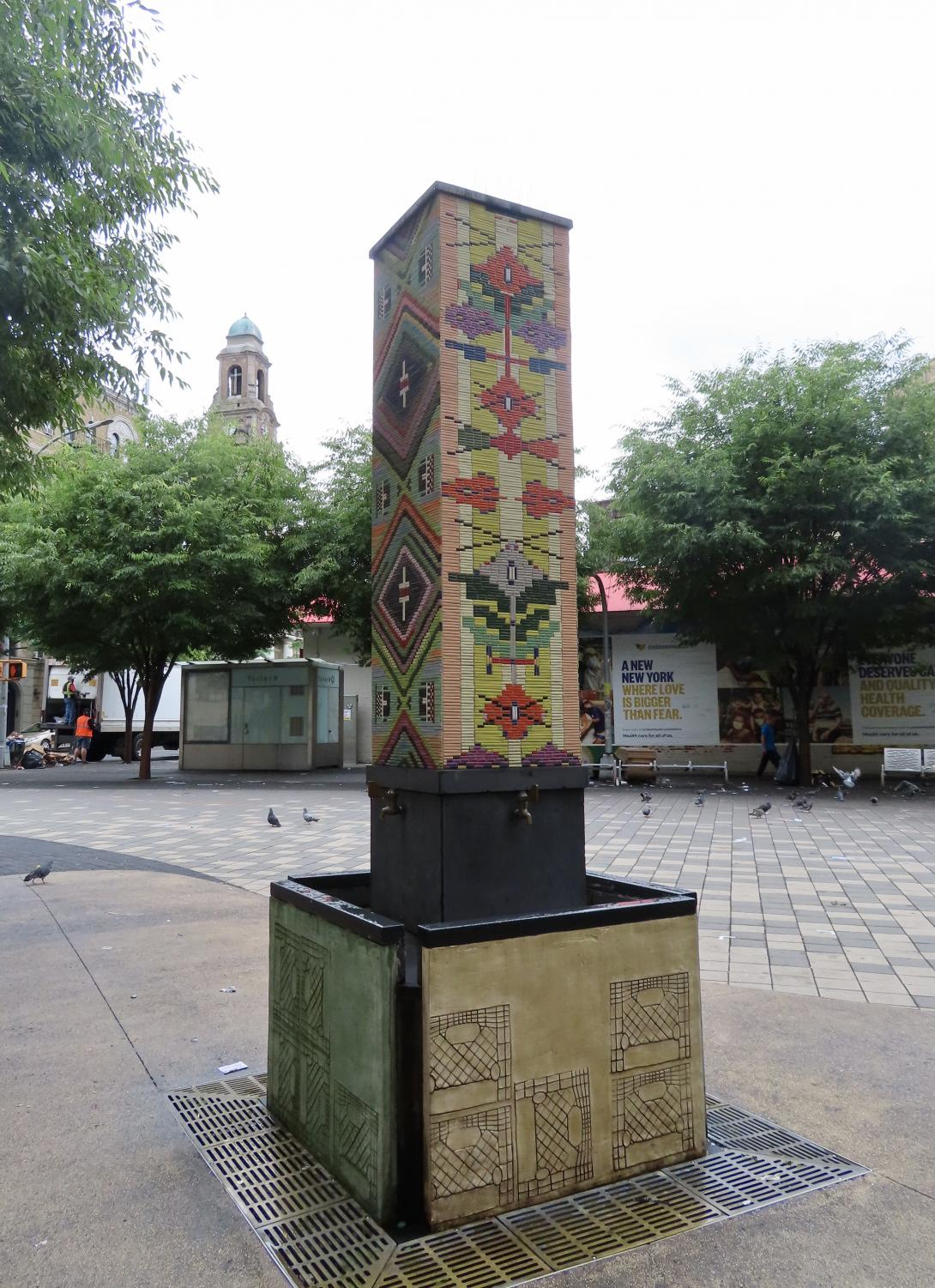a ceramic tiled fountain, that is tall and rectangular, in a Spanish style