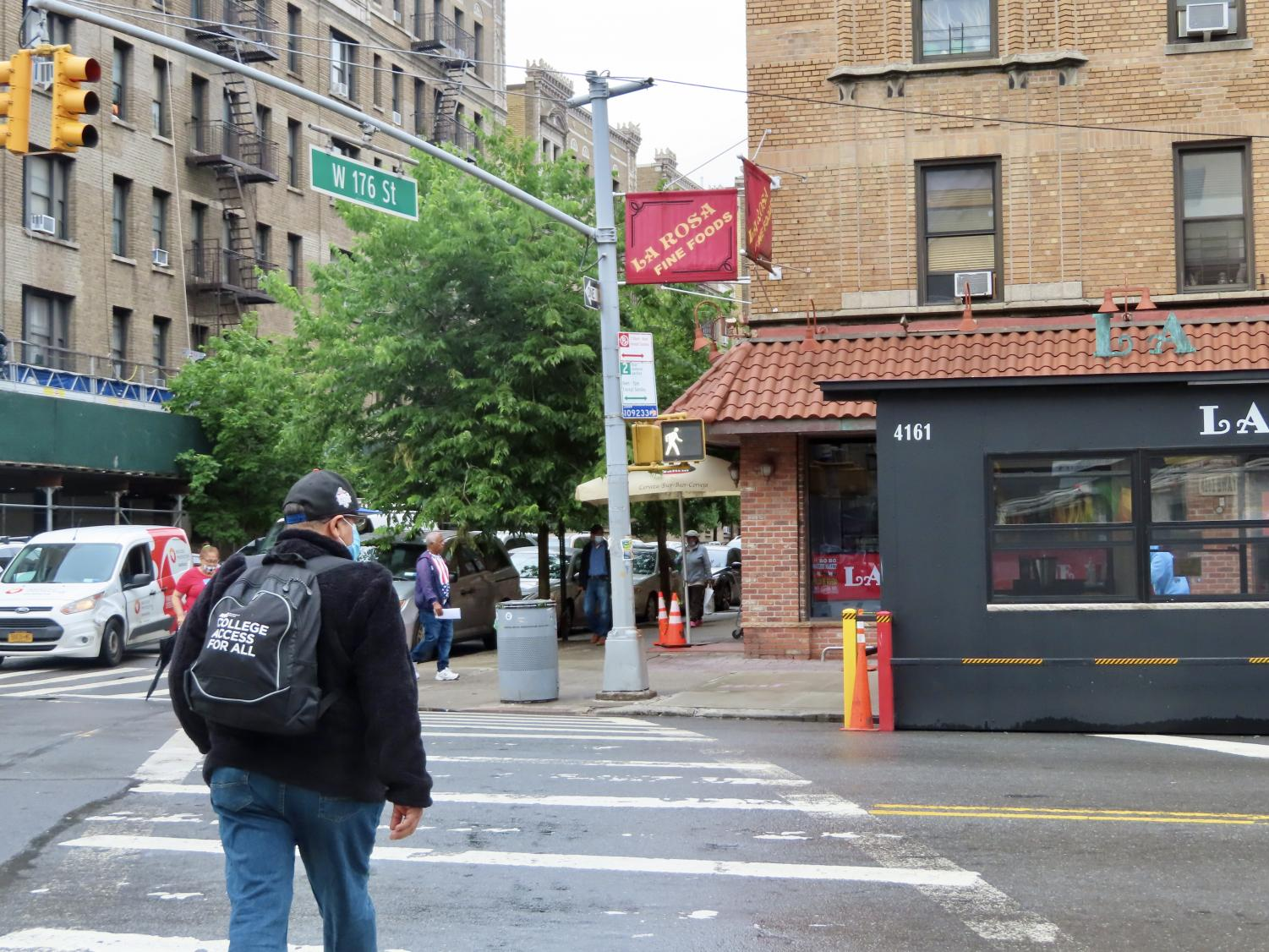 a pedestrian crossing Broadway at 176th street, walking toward a grocery store named La Rosa