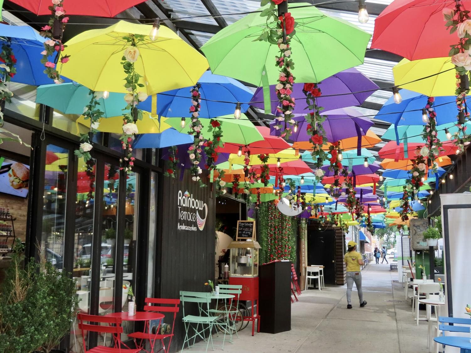 a restaurant called the Rainbow Terrace is pictured from the outside, with many umbrellas over outdoor seating