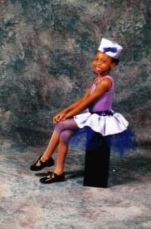 Minga Prather, age 5, sits in front of a gray background in a purple dance costume