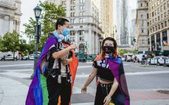 for an article about transgender housing on campus, two young people stand in NYC wearing pride flags on their backs