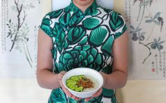 a woman in a green dress holds a bowl of congee made here in a Taiwanese style with garlic cucumbers and pork floss