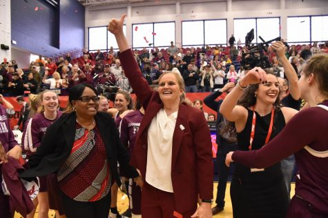 Sonia Burke stands next to Stephanie Gaitley. Both women are smiling and surrounded by the women's basketball team.