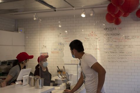 inside Fong On two workers and a person ordering, all wearing masks