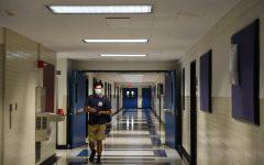 student wearing masks walks in a hallway in the Leon Lowenstein Center