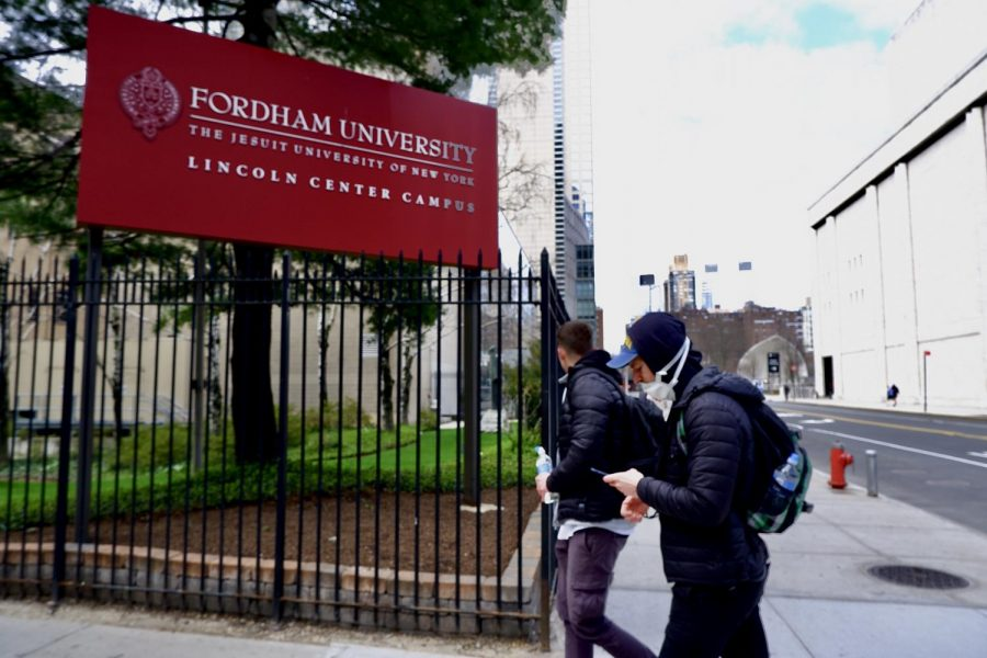 two individuals are walking in front of a sign reading Fordham University: The Jesuit University of New York while wearing masks