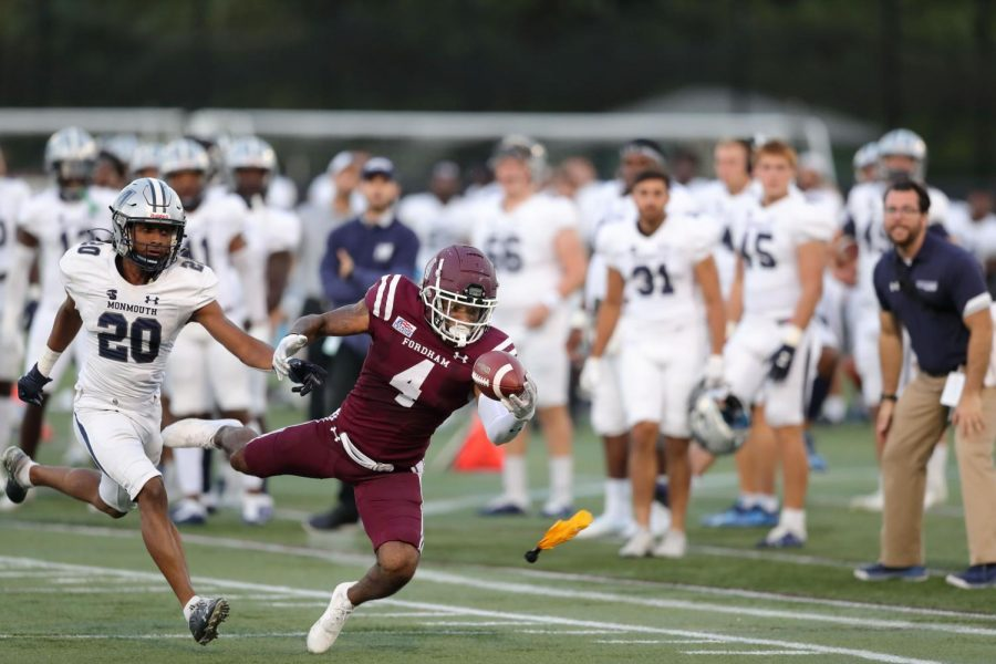 A Fordham football player catches a ball with one hand in front of many Monmouth players