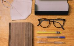 School supplies, glasses, and a mask laid out orderly on a wood table