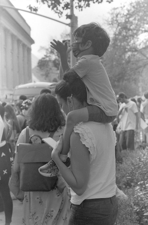 Child on his fathers shoulders trying to view the gala