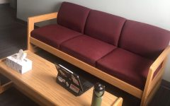 a couch and a laptop on a coffee table in a room designated for quarantine after students tested positive for COVID-19