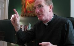 Rev McShane sits in an office and points while speaking
