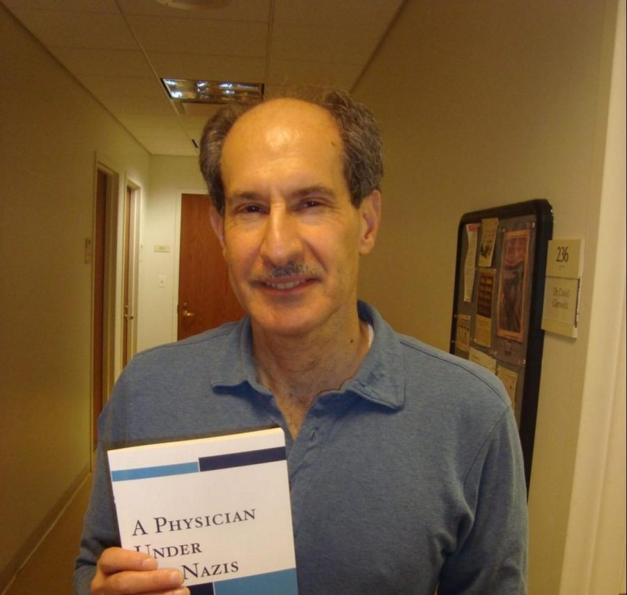 David Glenwick holding a book that he wrote