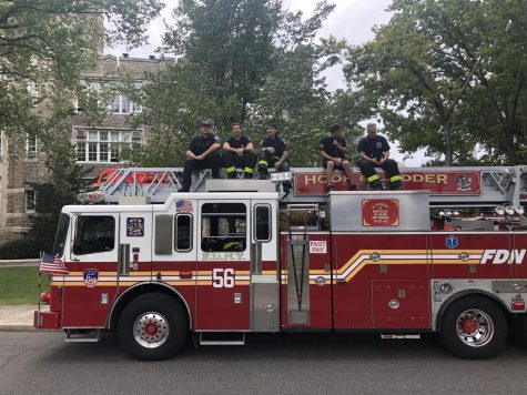 at the wagner game, firefighters sit atop their firetruck to watch the action