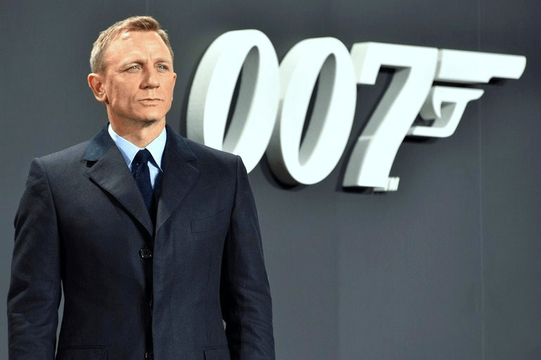 Daniel Craig standing in front of a 007 sign with a gun pointed out of the 7, a symbol of Craigs run as James Bond