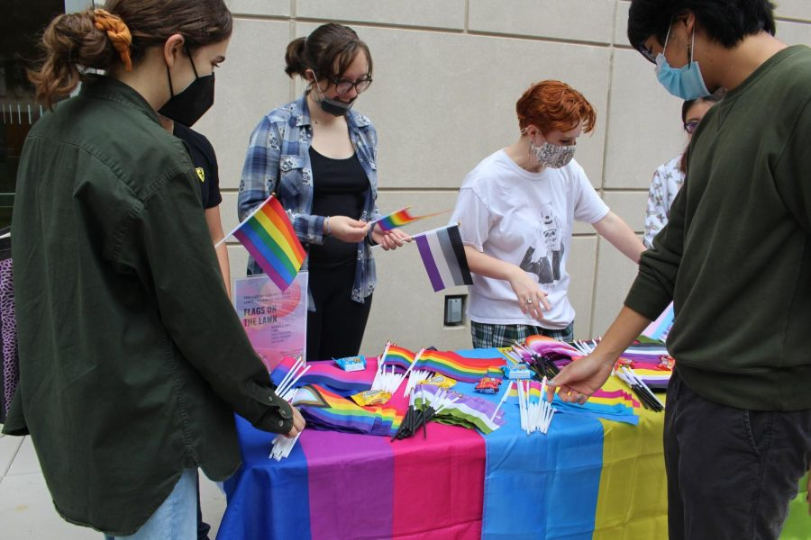 members of the lgbtq+ history month committee give out flags for the office of multicultural affairs event