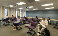 students sitting in a Fordham classroom wearing masks