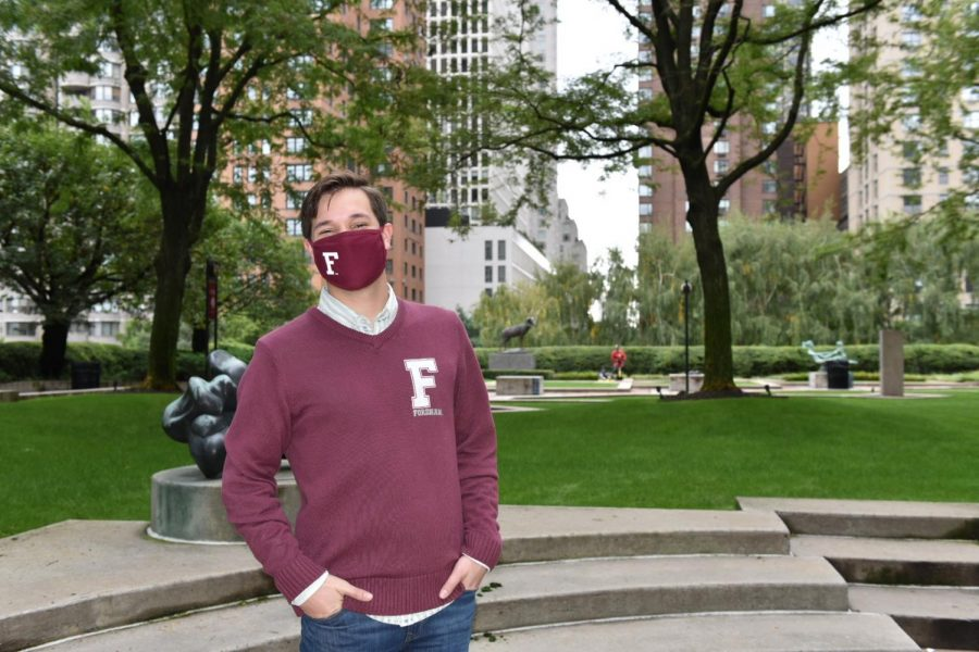 Robert Sundstrom stands in a plaza, wearing a maroon Fordham sweater and a mask with an F on it