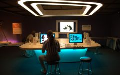 people sitting at a desk with blue light surrounding them