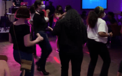 at mucho gusto hosted by SOL at fordham, students dancing with pink and purple lighting
